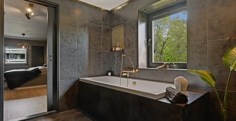 Delikat og innbydende hovedbad med sorte fliser på vegger og gulv