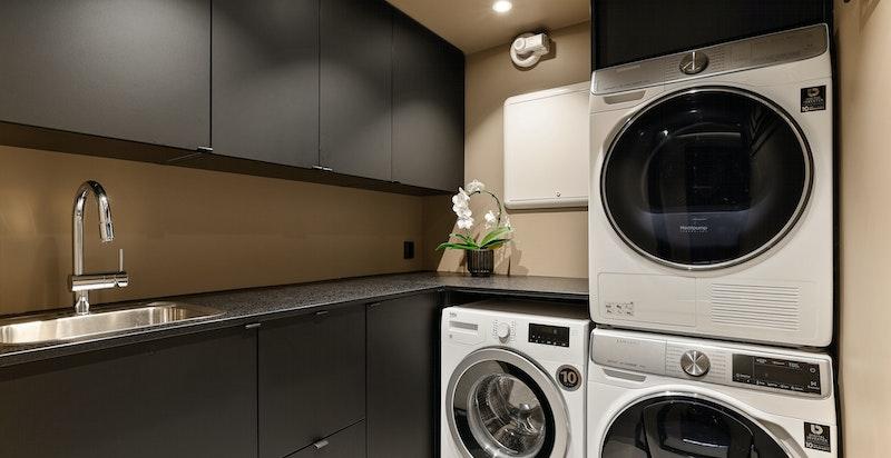 Pent og praktisk vaskerom med Innredning fra Kvik med sorte fronter på under-/og overskap
