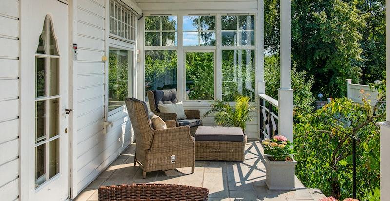 Fra terrassen i front med utg. fra stuen og nedgang til hagen