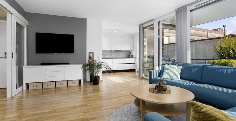 Romslig stue med praktisk delvis åpen løsning mot moderne kjøkken