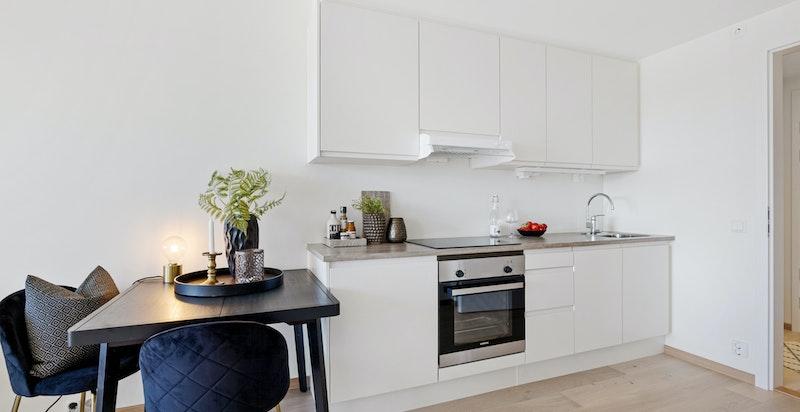 Kjøkkenet er praktisk designet og godt utnyttet med takhøye skap med foring.