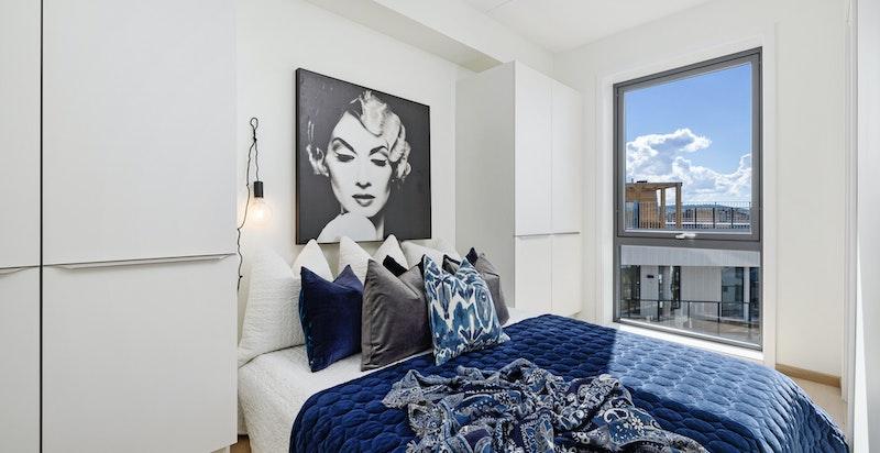 Lyst og luftig soverom med tilhørende garderobeløsning med skyvedører på hver side av sengen.