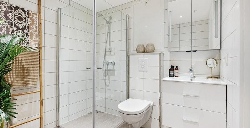 Moderne innredning med integrert belysning i speilskap, samt opplegg til vaskemaskin/tørketrommel i søyle.