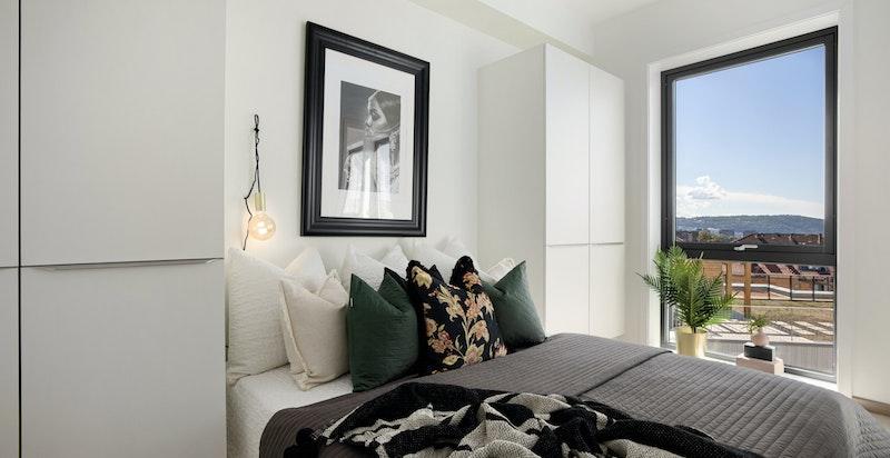Lyst og luftig soverom med tilhørende garderobeløsning.