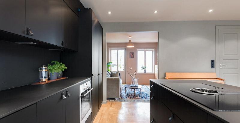 Kjøkken mot tv-stue. Stram kompakt laminat benkeplate og moderne koketopp med integrert ventilator.