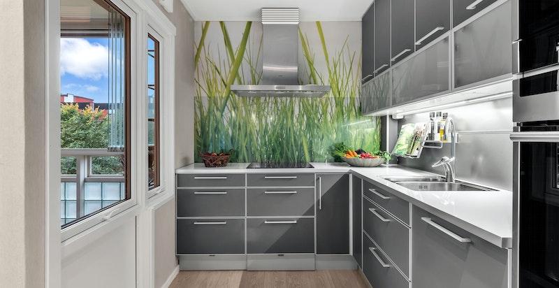Moderne og tiltalende kjøkken fra HTH med grå glatte fronter og grå laminat benkeplate i flott kombinasjon.