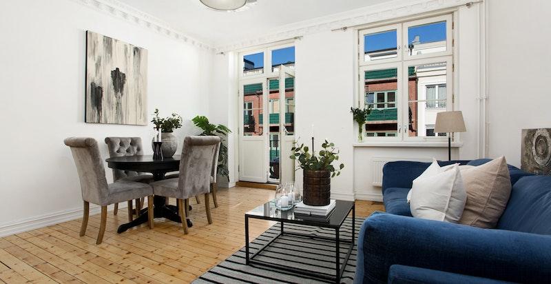 Romslig stue med plass for både salong og spisebord. Utgang balkong med ettermiddagssol