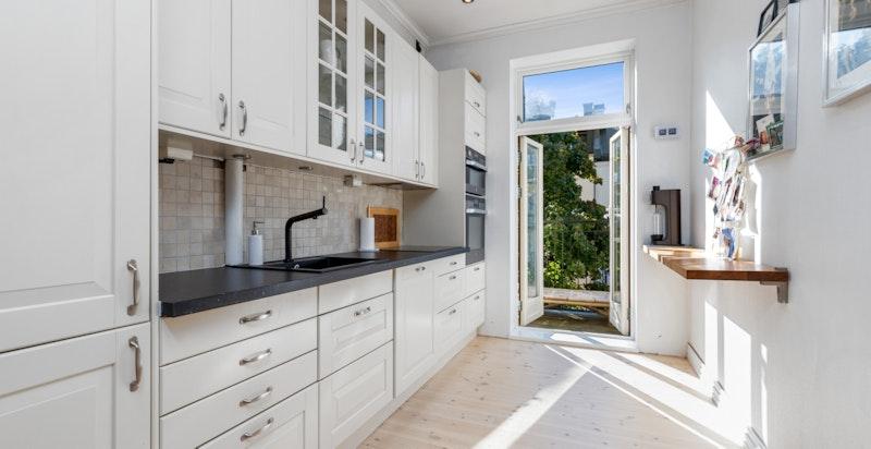 Moderne kjøkken med utgang til solrik balkong