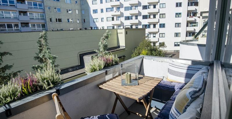 Hyggelig balkong mot grønn bakgård med gode solforhold