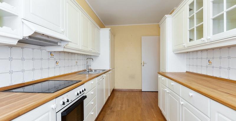 Kjøkkenet er innredet med skuffer og skap, benkebebysning og veggfliser over kjøkkenbenkene.
