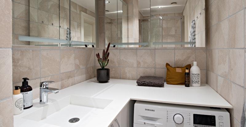 Pent flislagt bad med opplegg for vaskemaskin