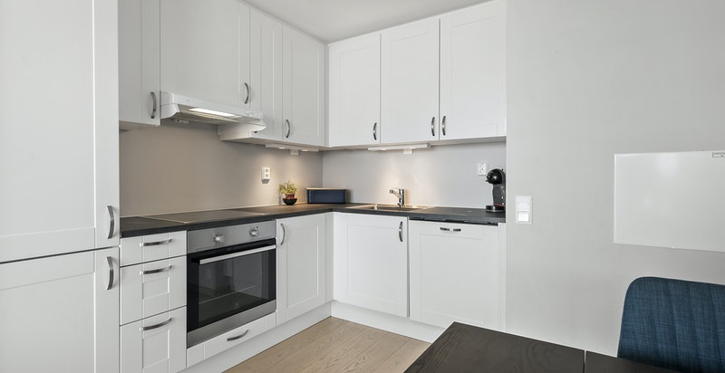 Delikat kjøkkeninnredning med hvite profilerte fronter og koksgrå benkeplater