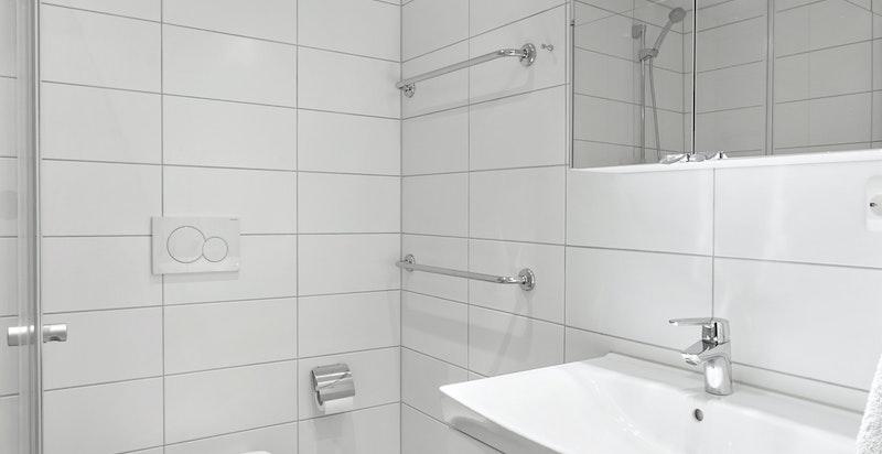 Badet er innredet med servantskap, dusj med innfellbare dører og vegghengt toalett