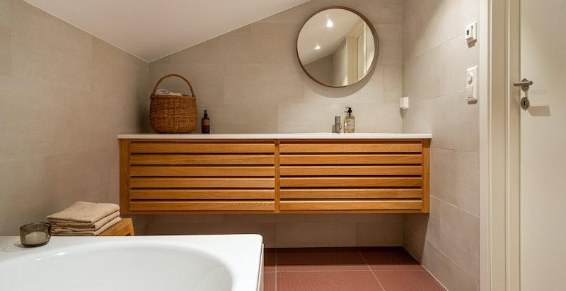 Baderommet har badekar og uno form baderomsinnredning.