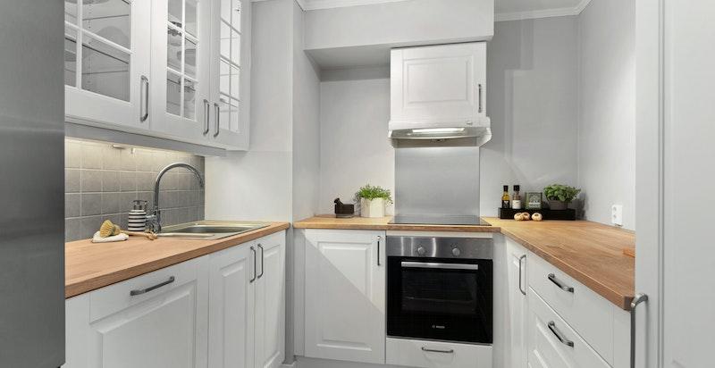 Kjøkkeninnredning med hvite profilerte fronter på skuffer og skap, samt vitrinedører på overskap