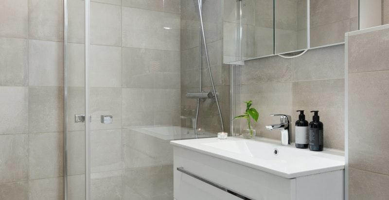 Dusjnisje med svingbare dører i herdet glass vegghengt innredning med skuffer, samt speilskap med integrert belysning