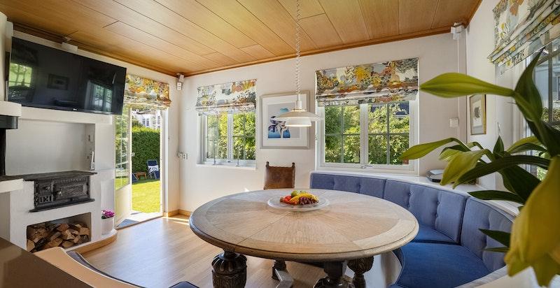 Spiseplass ved kjøkken har likhet med stuen peis og utgang til terrasse/hage