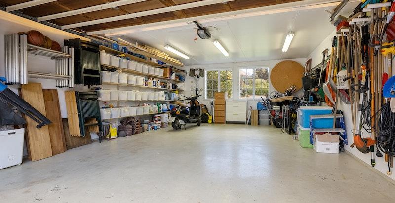 Dobbel garasje med vinduer og hyller for effektiv oppbevaring. Epoxi på gulv for enkelt vedlikehold.