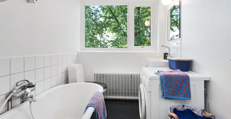 Romslig bad med badekar og nydelig grønn utsikt