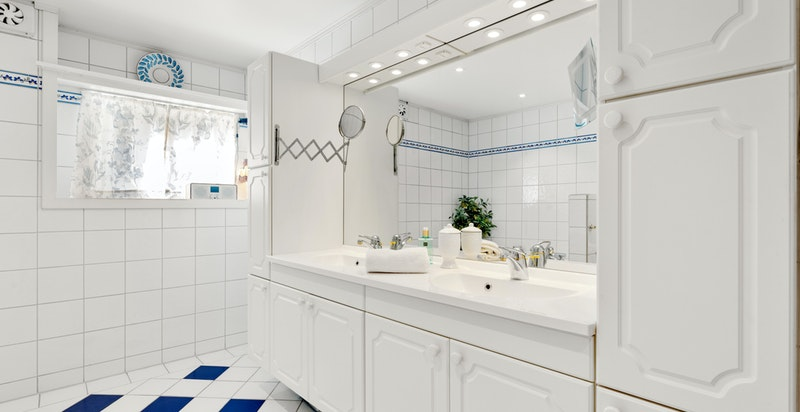 Stort, flislagt bad med badekar og dusj