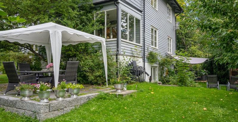Flere solrike uteplasser, gress og prydbusker gjør dette til en perfekt familiebolig.