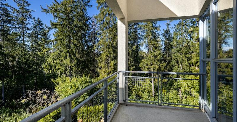 Romslig balkong med fredelig utsyn rett mot friareal og skogen