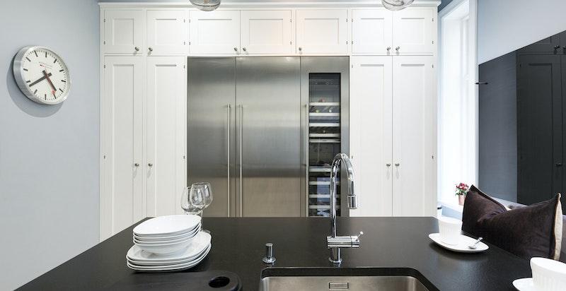 Eksklusiv plassbygget kjøkkeninnredning fra Lidhults. Benkeplater i sort granitt, integrerte hvitevarer fra Gaggenau.