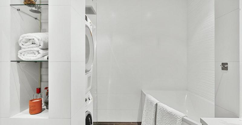 Romslig baderom med innmurt badekar, fossefallsdusj og blandebatterier fra Dornbracht