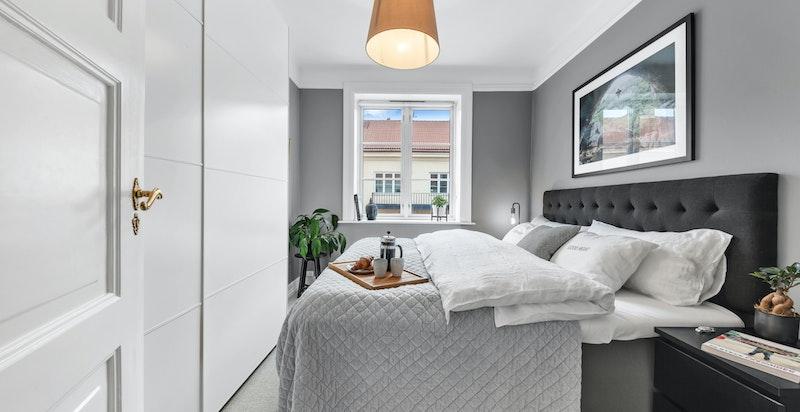 Romslig hovedsoverom med god plass til stor dobbeltseng med nattbord på begge sider