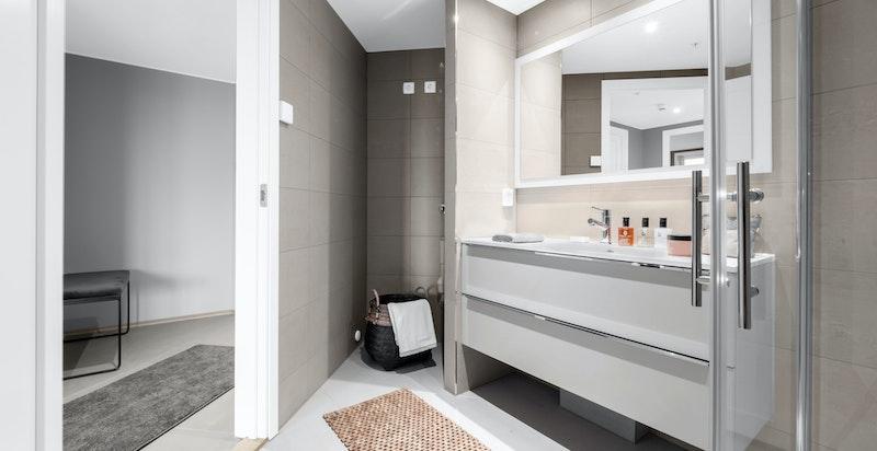 Pent baderom med italienske fliser og moderne vvs-utstyr. Varme i gulv, downlights i himling. Vaskesøyle ses lengst bak i bildet.