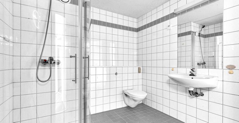 Badet er innredet med vask, ettgreps blandebatteri, speil, vegghengt toalett og dusjhjørne med innfellbare dusjvegger i glass.