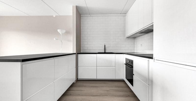 Kjøkkenet er velutstyrt med sort antrasitt oppvaskkum med sort ettgreps blandebatteri, fliser over benk og ventilator over koketopp.