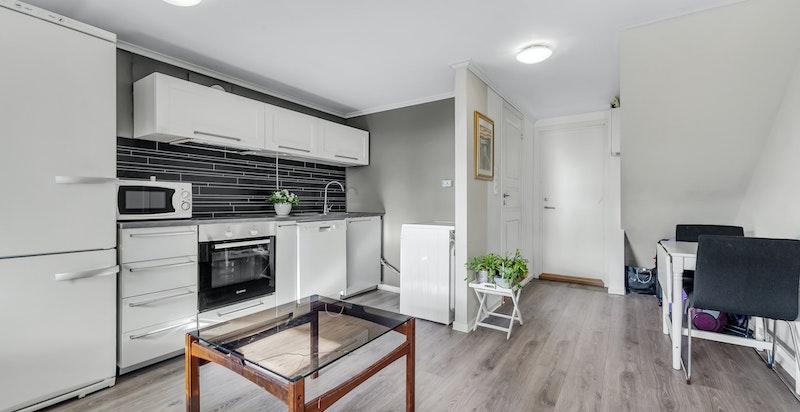 Kjøkkeninnredning med grå glatte fronter på skuffer og underskap. Hvite profilerte fronter på overskap.. Benkeplate med nedfelt oppvaskkum med avrenningsfelt i rustfritt stål. Integrert koketopp og stekeovn