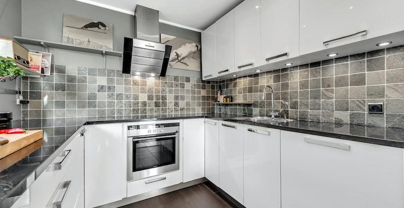 Benkeplater i sort polert granitt. Integrert planlimt induksjonstopp, stekeovn, oppvaskmaskin og kjøleskap. Kjøkkenventilator er montert på vegg over kokesone tilkoblet kanal ut over tak