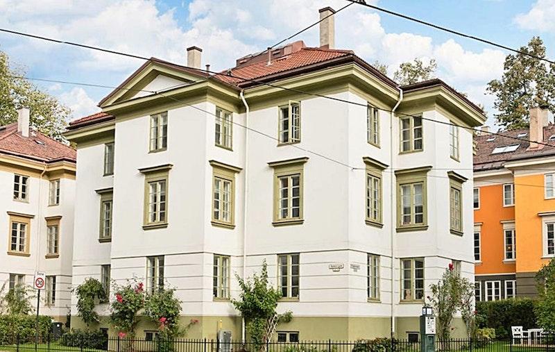 Klassisk fasade med idyllisk hage med sittegruppe - sjarmerende inngangsparti til eiendommen