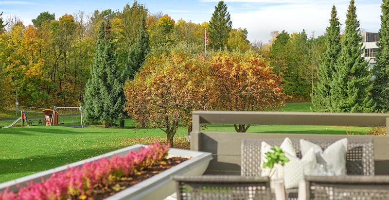 Fra terrassen er det flott utsyn over sameiets parkmessige fellesarealer.