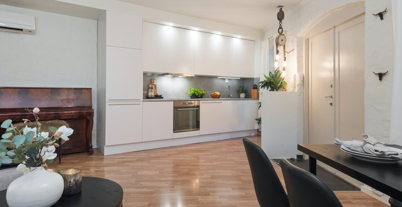 Lys og pen stue med åpent kjøkkendesign