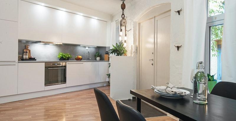 Stilrent kjøkken med ny benkeplate, spotter over overskap og integrerte hvitevarer