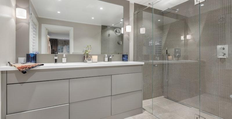 Badet inneholder frittstående badekar, elektrisk avtrekksvifte, servant med underskap og blandebatteri, dusjhjørne med innfellbare dusjdører