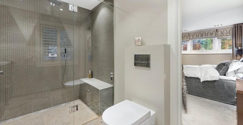 Delikat bad/wc pusset opp i 2015.  Badet ligger innenfor hovedsoverommet, og inneholder stor dusjnisje med to dusjbatterier, veggmontert wc, elektrisk avtrekksvifte, to servanter med underskap og blandebatteri