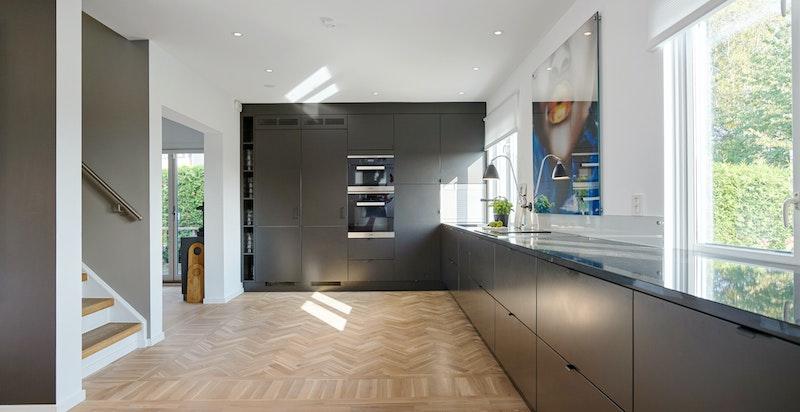 Lekker Strai kjøkkeninnredning fra 2018 med glatte, mørke fronter og granitt Nero benkeplate.