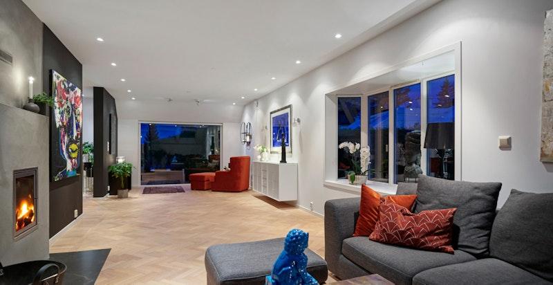 Stuen har flere innredningsmuligheter og peis som gir lunhet til rommet.