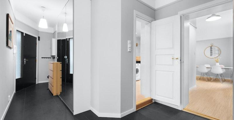 Hall/entré med flis på gulv. Godt med lagring i garderobeskap