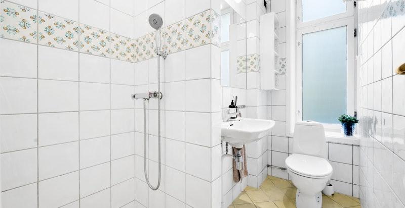 Bad/wc 2:. Badet har varmekabler i gulv, dusjhjørne med sluk, toalett, ventil/avtrekk, veggmontert servant med blandebatteri