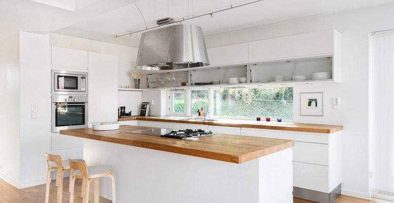 HTH kjøkkeninnredning med integrerte hvitevarer og benkeplate i heltre eik.