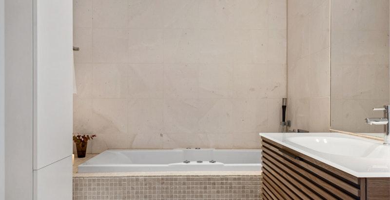 Leiligheten har to pene flislagte bad, ett med badekar.