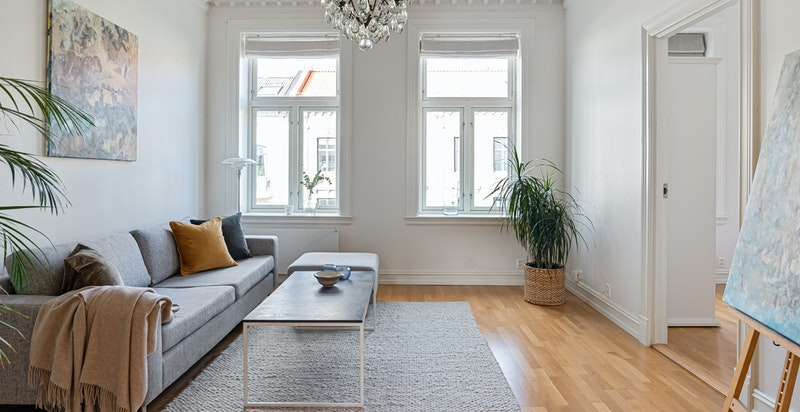Lys og hyggelig stue med store vindusflater, klassiske detaljer og varme i gulvene