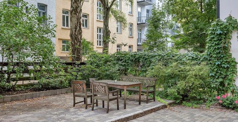 Eckersbergs gate 39 - miljø fra sommer. Hyggelig brostenslagt bakgård med sittegrupper