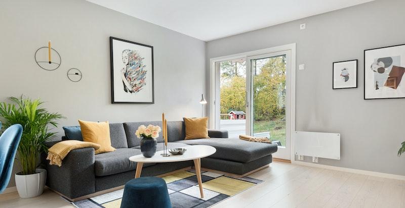Koselig salongdel i stue med utsikt til og dør ut til det flotte uteområdet