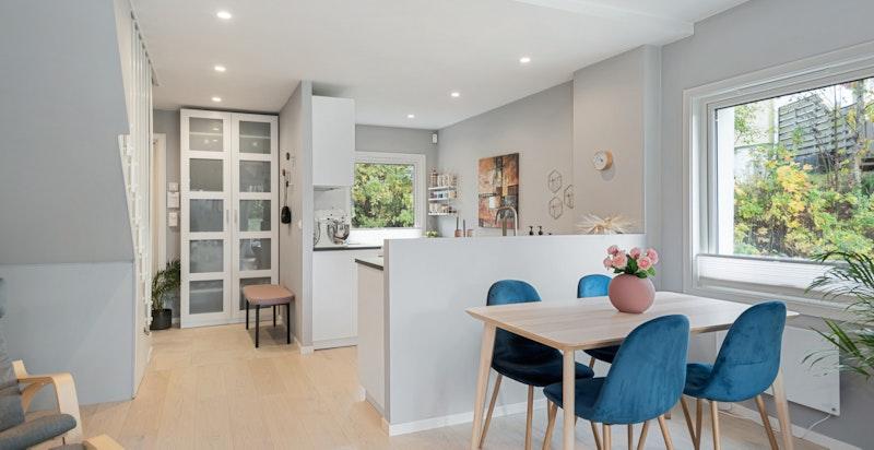 Hyggelig spiseplass ved kjøkkenet. Det er åpen løsning mellom rommene men en noe forhøyet vegg bak kjøkkenbenken skaper en praktisk skjerming